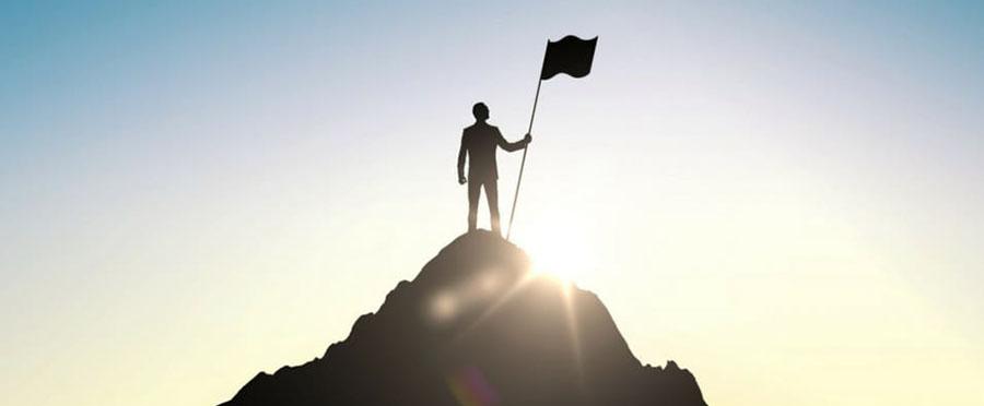 Мужчина на вершине горы с флагом
