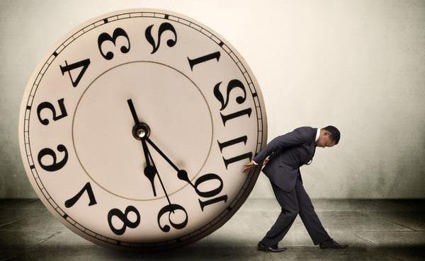 Работник толкает циферблат часов